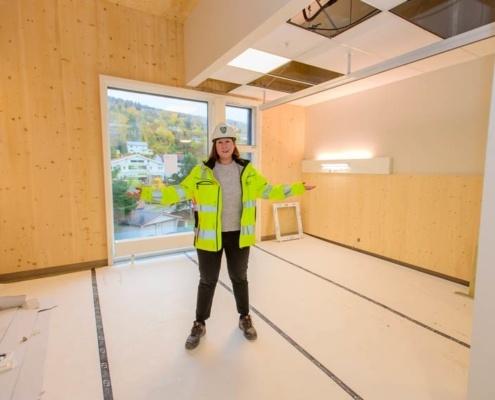 Prosjektkoordinator Ingeborg Engelien Andresen viser ett av de nye rommene, med vegger i massivtre.